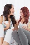Amis féminins gais causant au-dessus du café dans le lit Photographie stock libre de droits