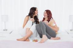 Amis féminins gais causant au-dessus du café dans le lit Image stock