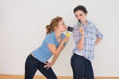 Amis féminins gais chantant dans des pinceaux dans une nouvelle maison Photo libre de droits