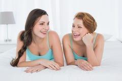 Amis féminins gais dans des dessus de réservoir de sarcelle d'hiver se situant dans le lit Images stock