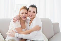 Amis féminins gais embrassant dans le salon Photos libres de droits