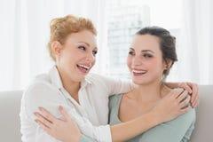 Amis féminins gais embrassant dans le salon Image libre de droits