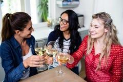 Amis féminins gais grillant le verre à vin à la table dans la maison Image libre de droits