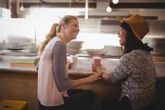 Amis féminins gais parlant tout en se reposant au café Image stock