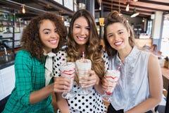 Amis féminins gais posant avec des boissons dans le restaurant Photo stock