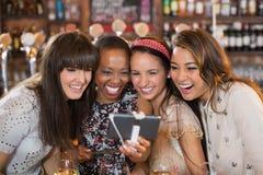 Amis féminins gais prenant le selfie dans le bar Image stock