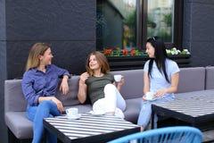Amis féminins gais riant et parlant au café, café potable Photographie stock