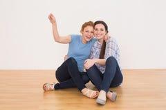 Amis féminins gais s'asseyant dans une nouvelle maison Image libre de droits