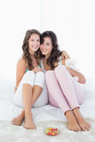 Amis féminins gais s'asseyant sur le lit avec le bras autour Photo libre de droits