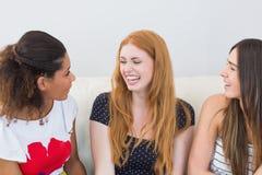 Amis féminins gais s'asseyant sur le sofa à la maison Image stock