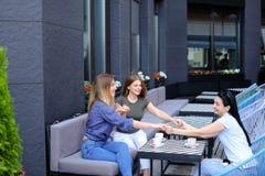 Amis féminins gais tenant des mains au café et buvant du café Photo libre de droits