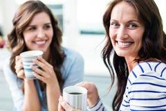 Amis féminins gais tenant des tasses de café tout en se reposant à la table Photo libre de droits