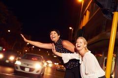 Amis féminins grêlant le taxi sur la rue de ville la nuit Images libres de droits