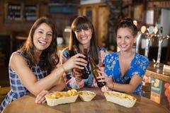 Amis féminins grillant des bouteilles à bière dans la barre Photographie stock libre de droits