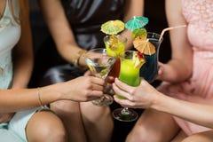 Amis féminins grillant des verres de cocktail dans la barre Photographie stock libre de droits