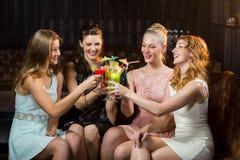 Amis féminins grillant des verres de cocktail dans la barre Image libre de droits