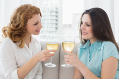 Amis féminins grillant des verres de vin à la maison Photographie stock libre de droits
