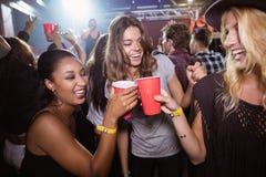 Amis féminins grillant les tasses jetables dans le club Photographie stock libre de droits
