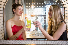 Amis féminins grillant un verre de cocktail dans la barre Image libre de droits