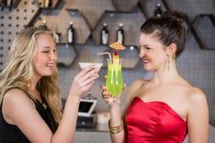 Amis féminins grillant un verre de cocktail dans la barre Images stock