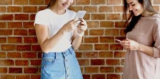 Amis féminins heureux à l'aide des smartphones Photos libres de droits
