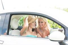 Amis féminins heureux à l'aide du comprimé numérique dans la voiture le jour ensoleillé Image stock
