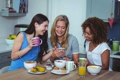 Amis féminins heureux à l'aide du smartphone Photo libre de droits