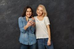 Amis féminins heureux à l'aide du smartphone au fond foncé de studio Images stock