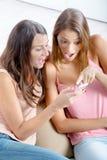 Amis féminins heureux à l'aide du téléphone portable à la maison Photos libres de droits