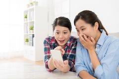 Amis féminins heureux à l'aide du téléphone portable mobile Photos stock