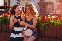 Amis féminins heureux écoutant la musique utilisant les écouteurs et le smartphone par le café sur la rue de ville jeunes de femm Photographie stock libre de droits
