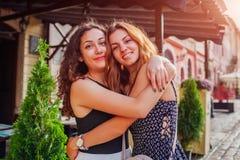 Amis féminins heureux étreignant sur la vieille rue de ville en été Vraies émotions des meilleures amies de femmes Images stock