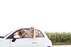 Amis féminins heureux appréciant dans la voiture contre le ciel clair Images stock
