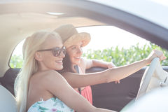Amis féminins heureux appréciant dans la voiture le jour ensoleillé Photo stock