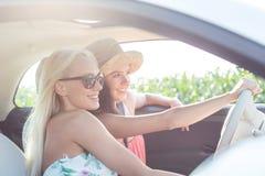 Amis féminins heureux appréciant dans la voiture le jour ensoleillé Image libre de droits