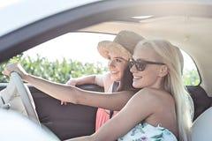 Amis féminins heureux appréciant dans la voiture le jour ensoleillé Images stock