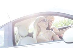 Amis féminins heureux appréciant le voyage par la route dans la voiture le jour ensoleillé Photo libre de droits