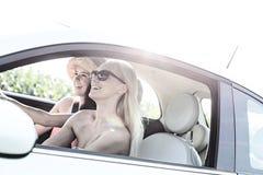 Amis féminins heureux appréciant le voyage par la route dans la voiture le jour ensoleillé Photos stock