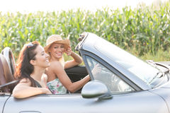 Amis féminins heureux appréciant le voyage par la route dans le convertible Photographie stock libre de droits