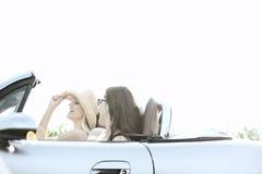 Amis féminins heureux appréciant le voyage par la route dans le convertible le jour ensoleillé Images stock