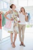 Amis féminins heureux avec des paniers au magasin d'habillement Photo stock