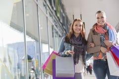 Amis féminins heureux avec des paniers marchant par le magasin Images stock