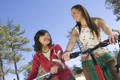 Amis féminins heureux avec des vélos de montagne Photo libre de droits
