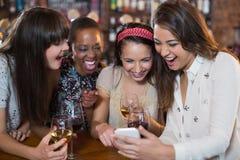 Amis féminins heureux avec des verres à vin utilisant le téléphone portable Images stock
