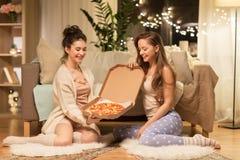 Amis féminins heureux avec la pizza à la maison Photographie stock libre de droits