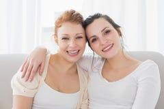 Amis féminins heureux avec le bras autour dans le salon Images libres de droits