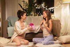 Amis féminins heureux avec le cadeau de Noël à la maison Photo stock