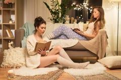 Amis féminins heureux avec le livre et le journal intime à la maison Images libres de droits