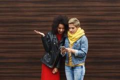 Amis féminins heureux avec le smartphone dehors Photographie stock libre de droits