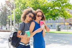 Amis féminins heureux avec le smartphone dehors Images stock
